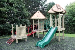 Wooden play towers with slide and bridge