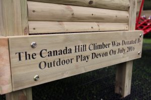 Engraved wood plaque at play area