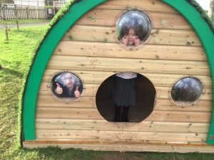 Kids look through windows in the wooden Play Pod