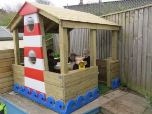 A wooden playhouse with lighthouse theme