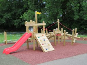 Wooden play tower equipment on safety surfacing