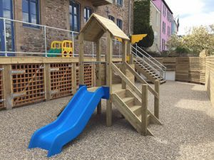Wooden play tower with plastic slide