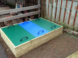 Raised wood framed sand pit for childrens play