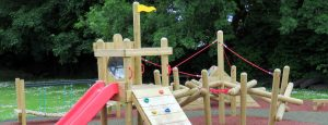 A wooden play tower with slide