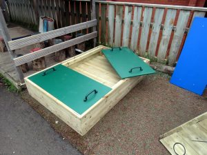 Raised wood framed sand pit with lid