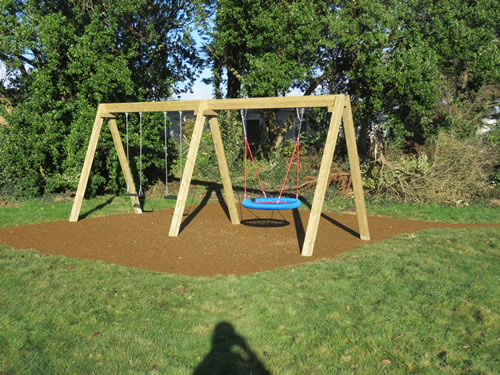 A birds nest swing installed on safety surfacing