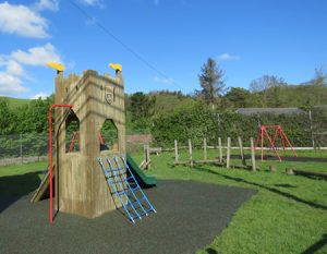 Wooden play tower in play space side view