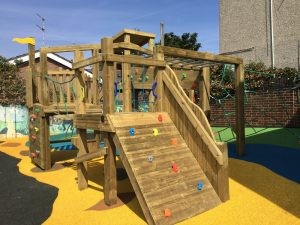 Wooden play climber with climbing wall