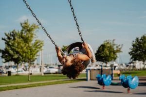 A young girl on s play swing outdoors