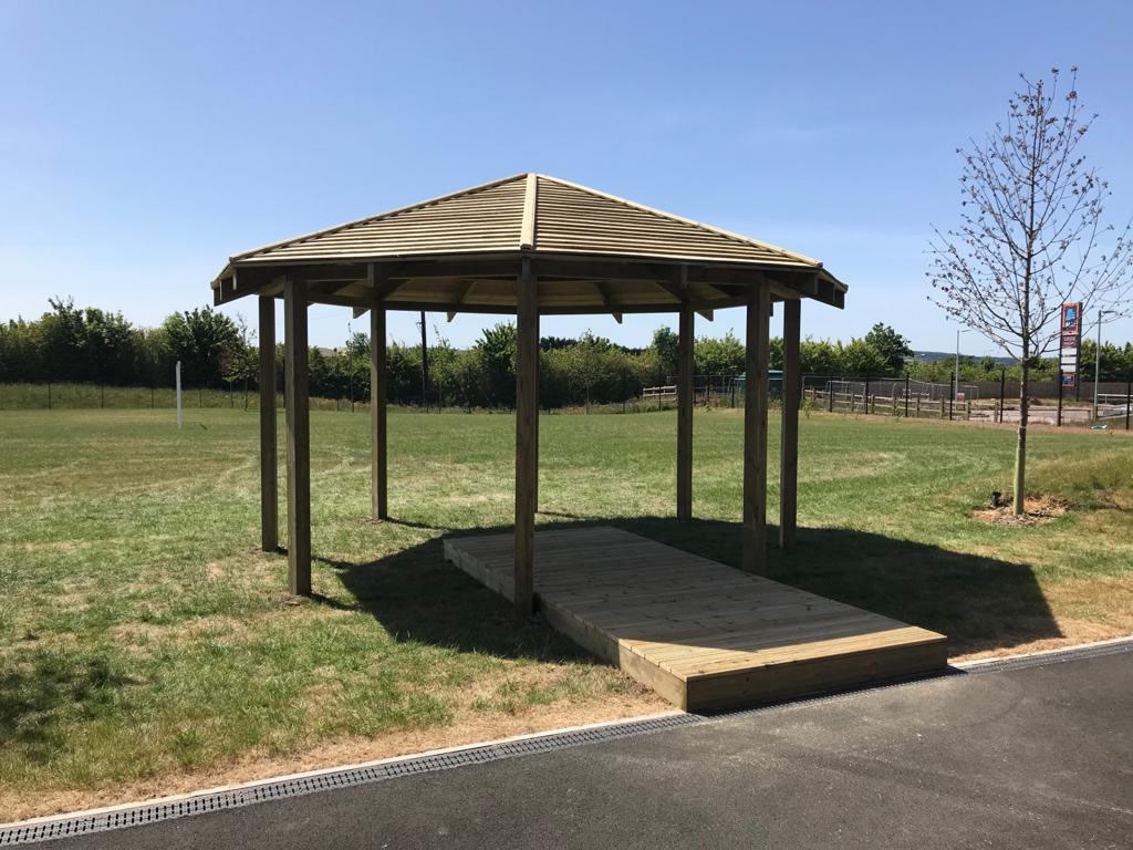 An open sided Dartmouth gazebo shelter with wooden decking