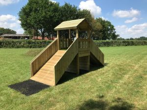A wooden play tower with ramps and tiled roof