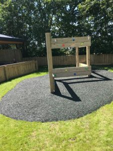 Outdoor play climbing wall with safety surfacing below