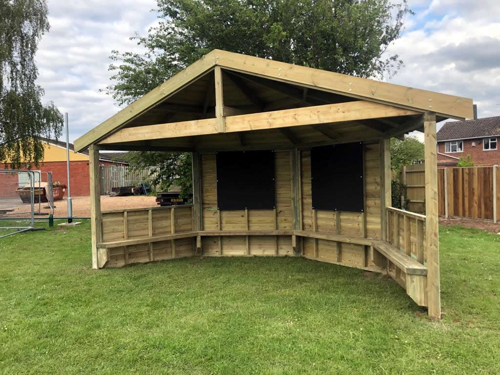 An open fronted wooden shelter for childrens school