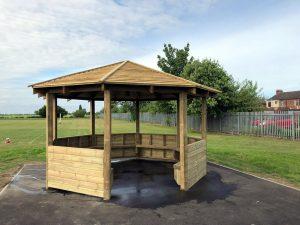 A wooden outdoor learnng shelter for children